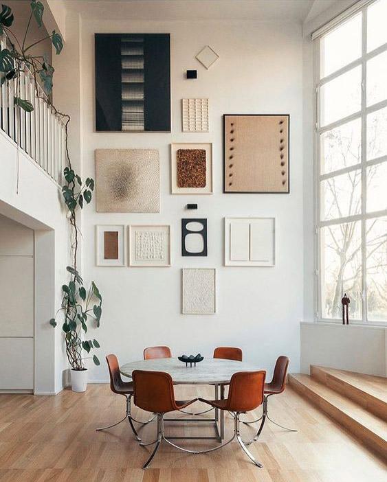 pared blanca con mosaico de obras de arte creando una galería en un comedor grande iluminada con ventana y mesa con seis sillas rojas