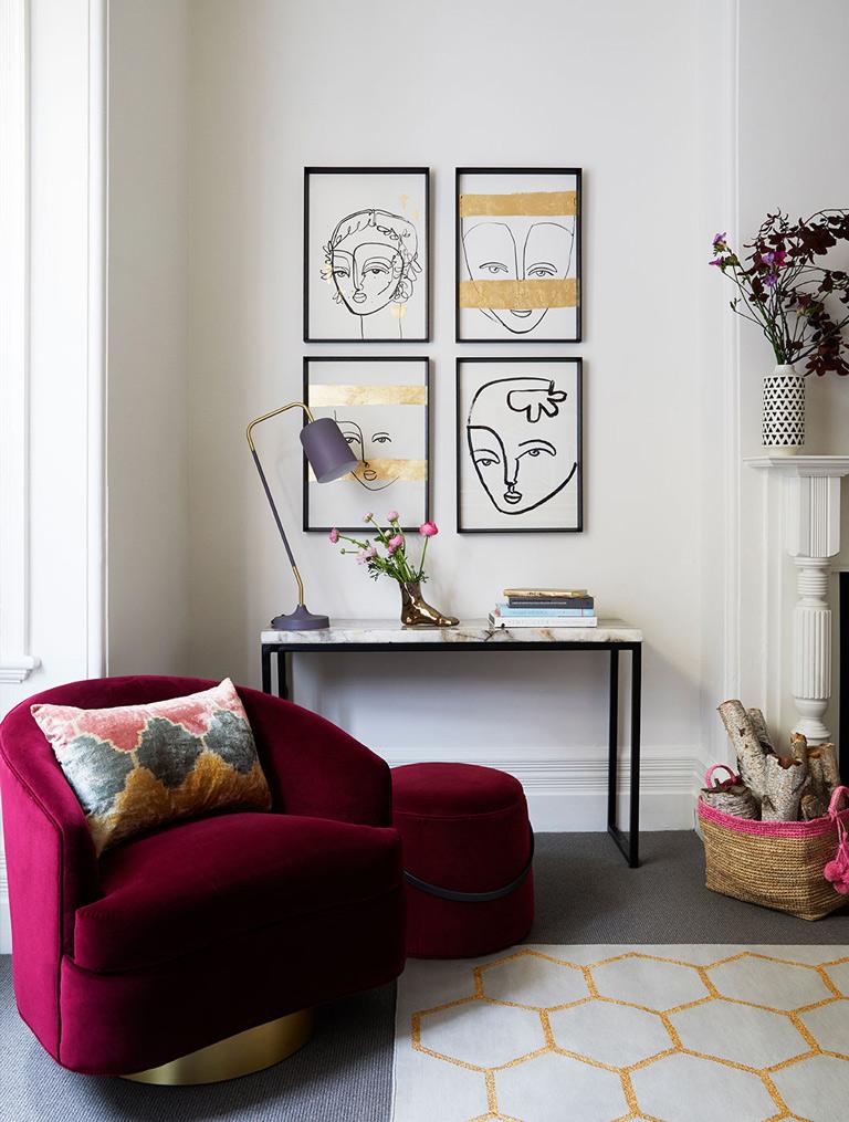 Pared con mosaico de cuatro láminas de dibujo con marcos negros en un rincón de salón con cónsola, sillón y taburete de terciopelo fucxia