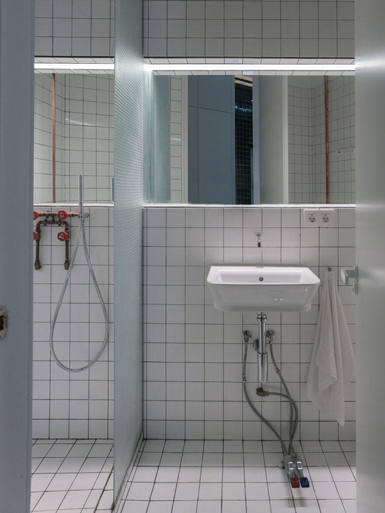 Cuarto de baño con alicatado blanco, instalaciones vistas, una pila con pedales y un espejo. Poppyns Magazine