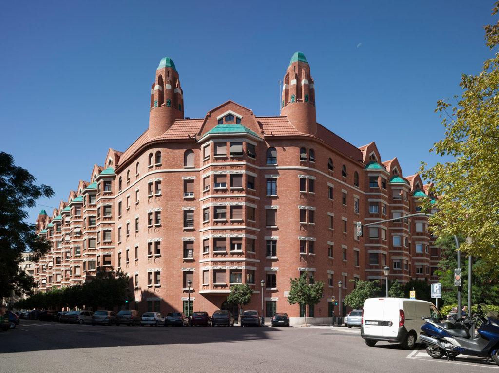 Edificio de fachada de ladrillo rojo visto, rematado con dos torres laterales. Fachada principal de la Finca Roja de Valencia. Poppyns Magazine