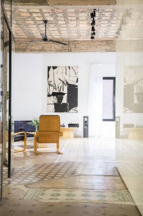 Estancia de edificio antiguo, con suelo de baldosa hidráulica, techos con forjado visto, mobiliario de diseño, cristal, forja, equipo de música y una pieza de arte en la pared. Poppyns Magazine