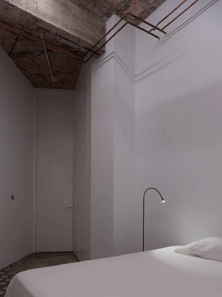 Habitación minimalista con paredes blancas, techos de hormigón, puerta sin dintel tan alta como la altura del techo, instalaciones vistas, una lámpara de pie de diseño y una cama de matrimonio. Poppyns Magazine