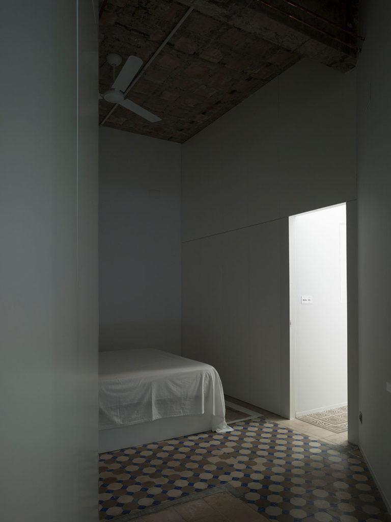 Habitación a oscuras con una cama y suelo de baldosa hidráulica, iluminada por la luz de un pasillo. Poppyns Magazine