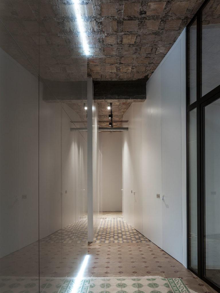 Pasillo de edificio antiguo, con suelo de baldosa hidráulica, techos con forjado visto y pared panelada en madera. Poppyns Magazine