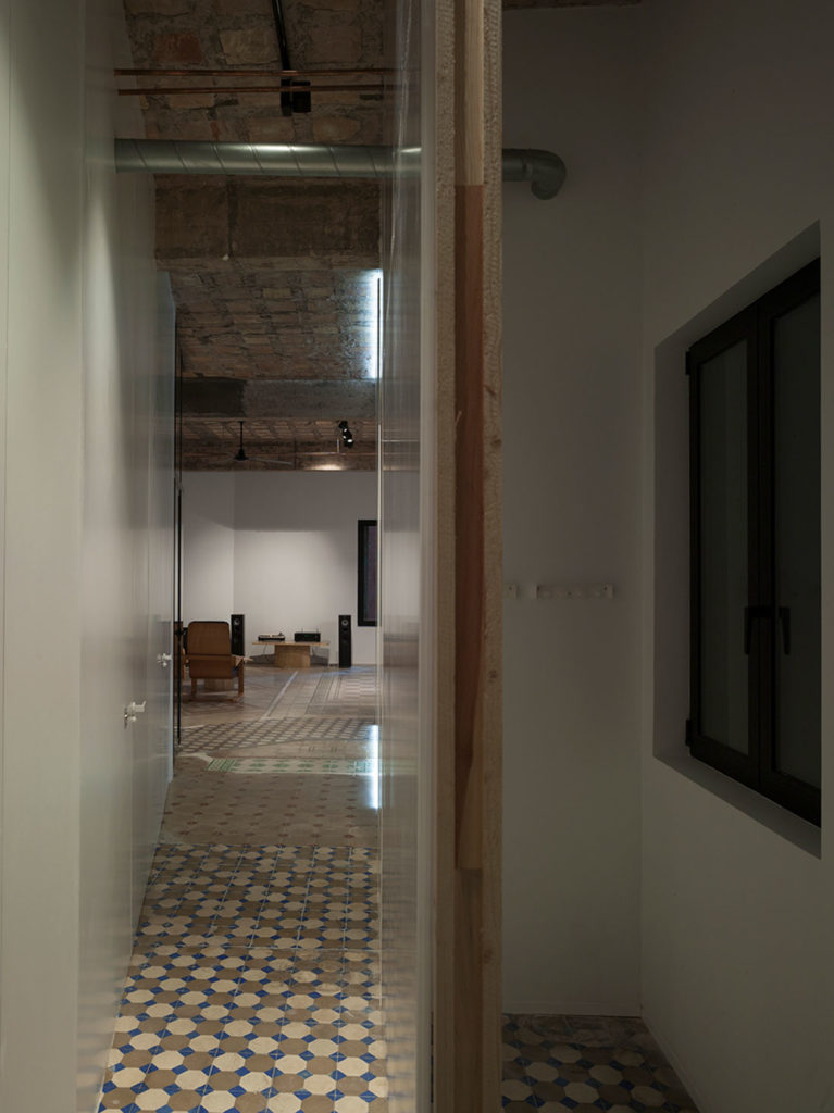 Estancia de edificio antiguo con suelo de baldosa hidráulica, techos con forjado visto, mobiliario de diseño y contraste de luces y sombras. Poppyns Magazine