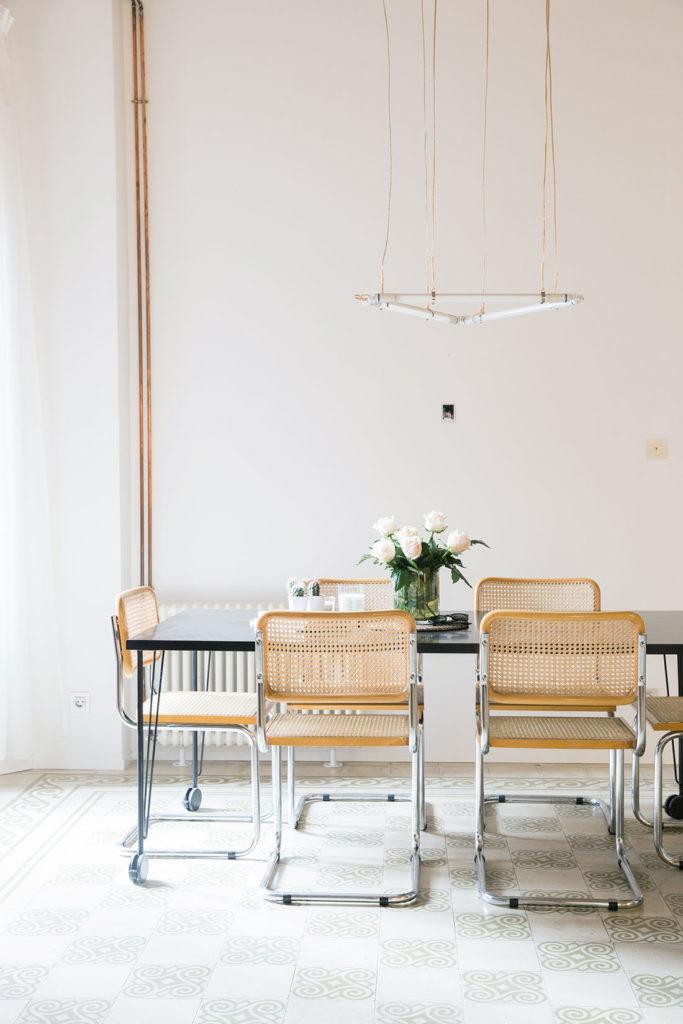 Sillas de mimbre y estructura metálica en torno a una mesa de madera oscura con ruedas, suelo de baldosa hidráulica en una habitación con instalaciones vistas y una lámpara colgante con forma de triángulo. Poppyns Magazine.