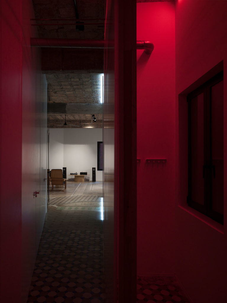 Estancia de edificio antiguo iluminada en rojo, con una sala al fondo con suelo de baldosa hidráulica, techos con forjado visto, mobiliario de diseño y contraste de luces y sombras. Poppyns Magazine