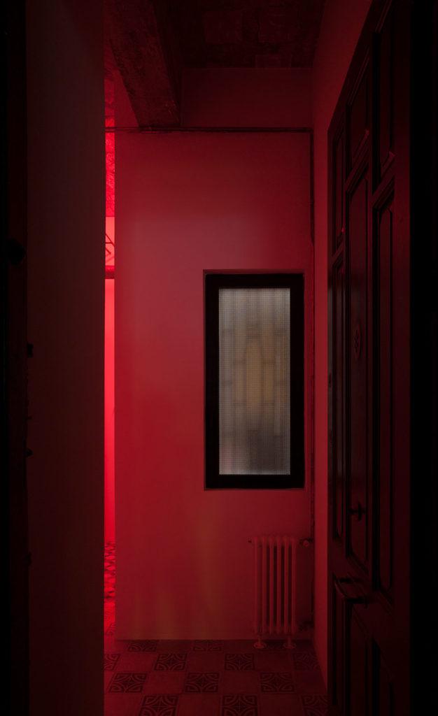Estancia de vivienda con una ventana, instalaciones vistas y luz roja. Poppyns Magazine