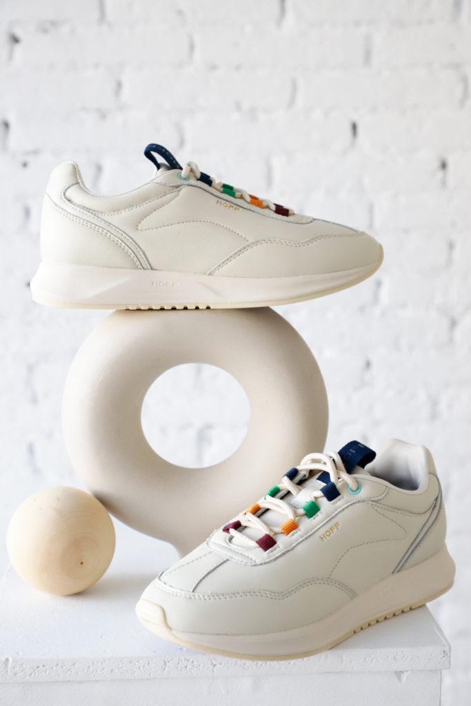 Bodegón con zapatilla clásica blanca y beige, multicolor de la marca española Hoff Brand sobre jarrón circular.