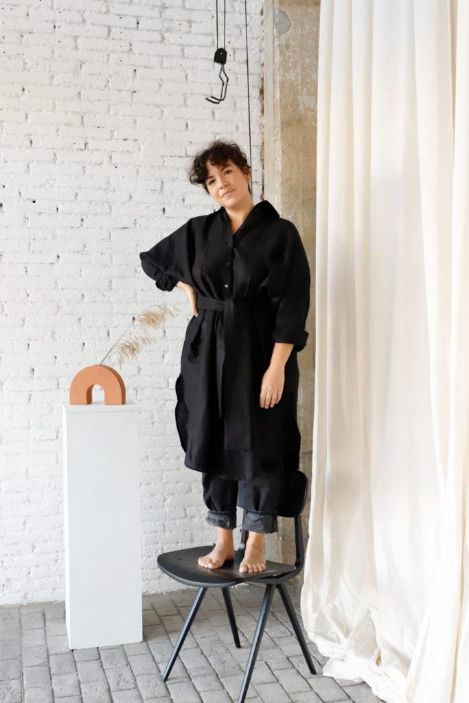 Alicia Macías subida a un taburete llevando el vestido Michelle de manga japonesa negro de la marca Lasastre, detrás jarrón de Pedrusco en color terracota.