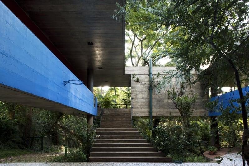 Edificio de hormigón en medio de un bosque con escaleras, una fachada de color azul y una canasta. Poppyns Magazine