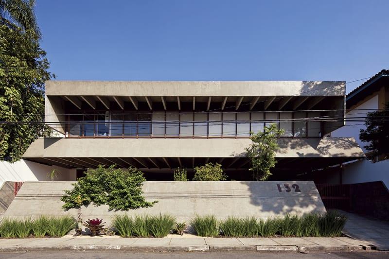 Fachada exterior de edifico de hormigón con el número 132 y con terraza con ventanales y entorno con jardín. Poppyns Magazine