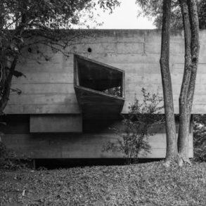 Fachada exterior de edificio de hormigón en blanco y negro con una ventana irregular. Poppyns Magazine