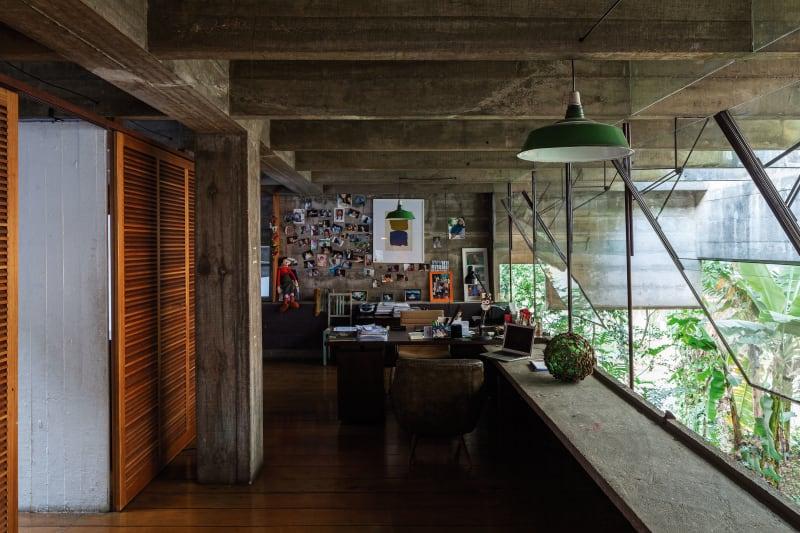 Interior de edificio de hormigón con ventanales que dan a un jardín y contraventanas de madera. Poppyns Magazine