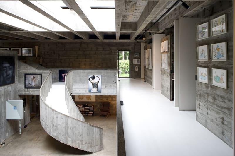 Interior de vivienda de hormigón con una escalera en curva, cuadros y un tragaluz. Poppyns Magazine