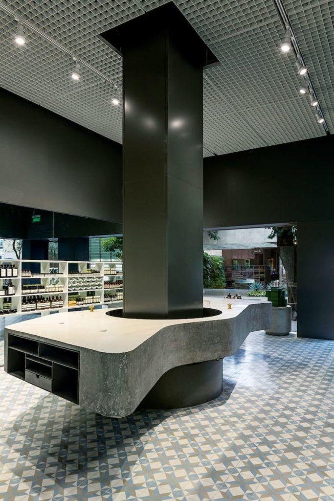 Interior de tienda de diseño minimalista con suelo de mosaico y una mesa con forma orgánica con un pilar en el centro. Poppyns Magazine