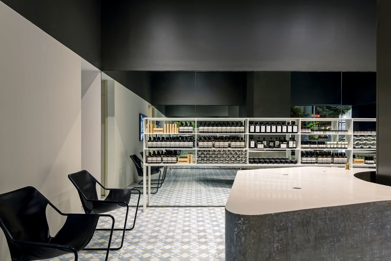 Interior de tienda de diseño minimalista con suelo de mosaico y estantería con productos. Poppyns Magazine