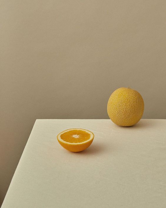 Bodegón en tonos crema con un limón y media naranja